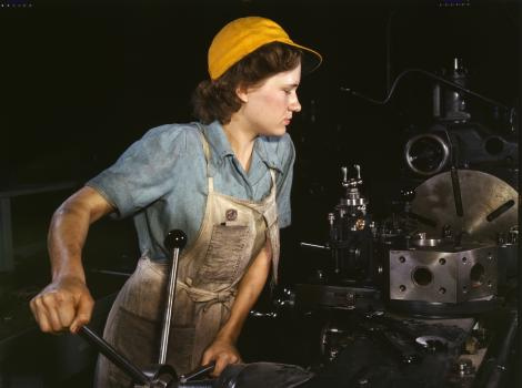(Lathe operator—woman in yellow hat)