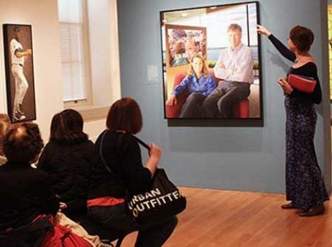 Adults listening to a docent talk about a painting