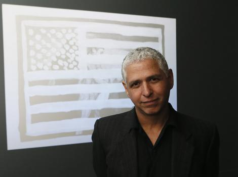 gray-haired man in front of a projection
