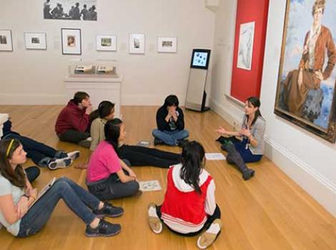 Students sitting on the gallery floor listening to a docent