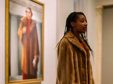 Teen girl in a fur coat standing before a portrait