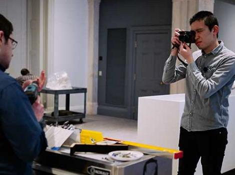 Photography intern taking photos of an exhibition being installed