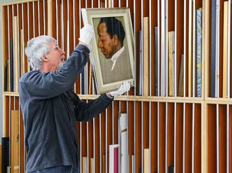 NPG staff member handling a portrait.