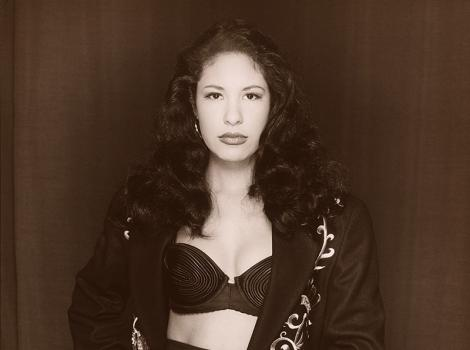 black and white photo of a woman with long dark hair in a bustier and patterned jacket