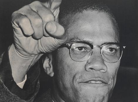 photo of a Black man with glasses speaking into a microphone