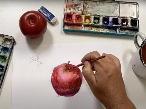 paint sets and a hand painting an apple