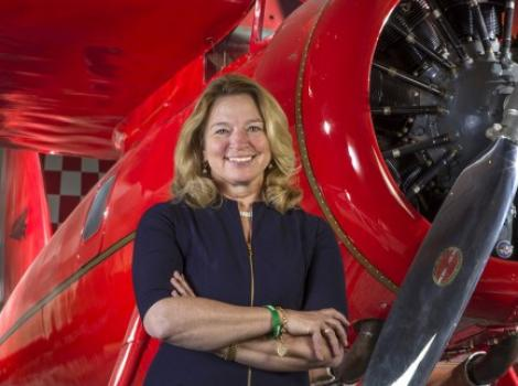 Woman in black standing in front of a red plane