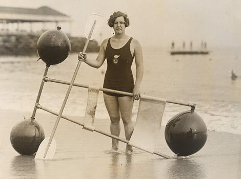 woman in a bathing suit on a beach with a flotation device