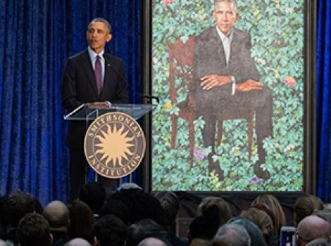 A man (Barack Obama) speaking at a podium in front of his portrait