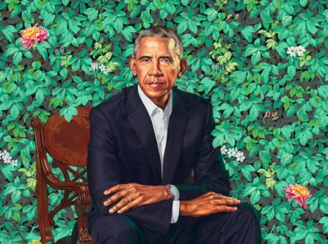 Man in a dark suit sitting in green foliage