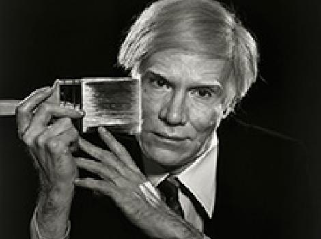 Balck and white portrait of a man in a blond wig with a paintbrush at his face.