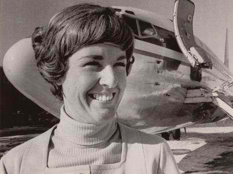 smiling woman in short hair standing in front of an airline