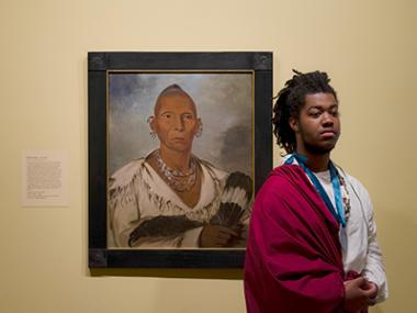 Young man portraying a Native American in front of a Native American portrait