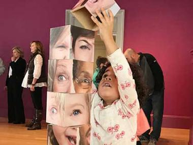 Child building a tower using blocks with photographs of faces on them