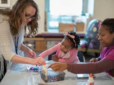 A teacher working on an art activity with two young kids.