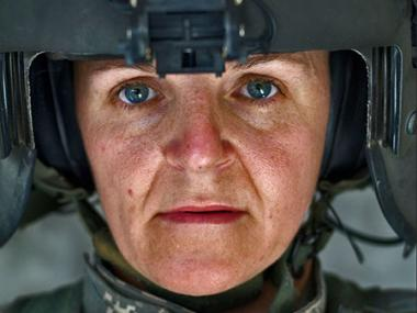 Close-up portrait of woman in helmet and combat fatigues