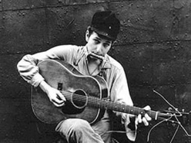 Photo of a young man in a black hat playing guitar and  harmonica