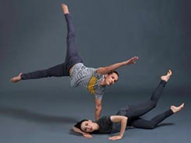 Male dancer balancing on one arm and female dancer lying on floor