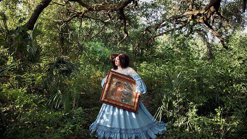 woman carrying a portrait through a southern landscape
