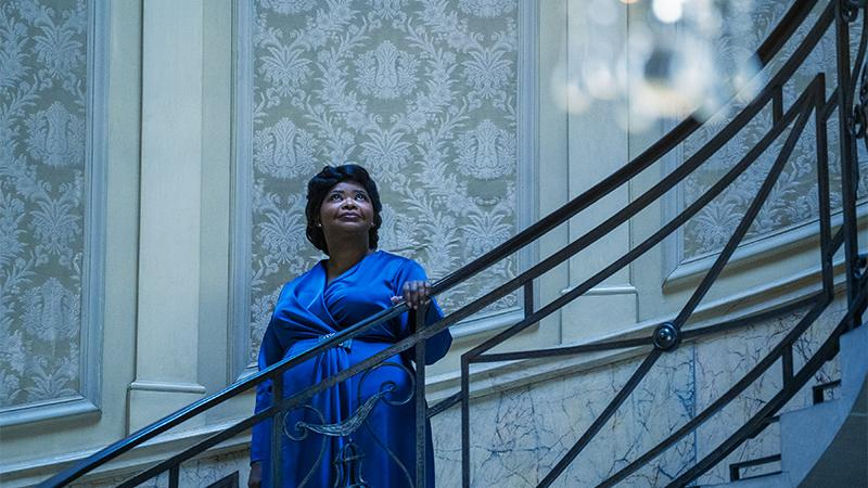 Woman in a blue dress standing on a staircase