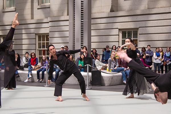 Un grupo de bailarines vestidos de negro, bailando