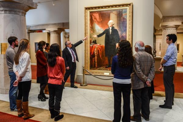Curador guiando una visita y señalando el retrato de George Washington