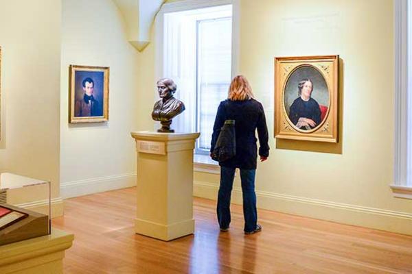 """Visitante mirando las pinturas en la galería de """"Orígenes estadounidenses"""""""
