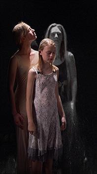 Three women in a darkened room