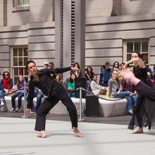 A group of dancers dressed in black, dancing