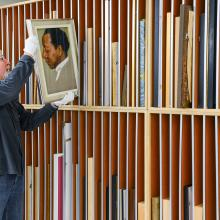 Man with taking a portrait from a rack of many artworks