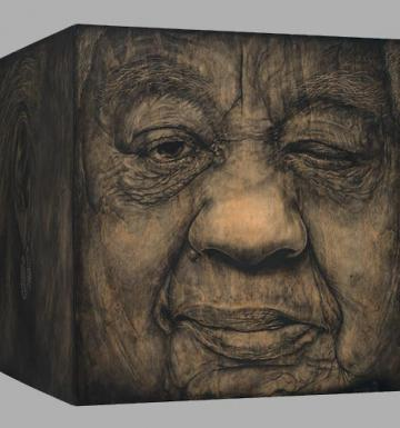 Old woman's face painted on a large cube, her head seen on four sides