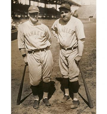 Old photograph of two baseball players leaning on their bats