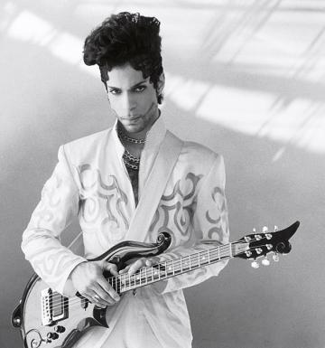 Black and white photograph of Prince holding a guitar