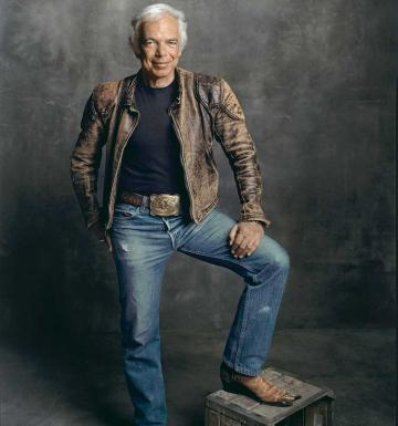 Man wearing jeans and a leather jacket with his cowboy-booted foot on a crate