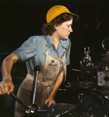 Color photograph of a woman working in a factory