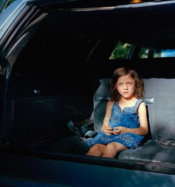LIttle girl with blue eyes and in a blue dress sitting in the backseat of an old car