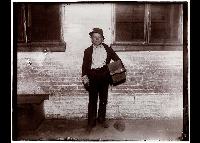 Black and white photo of a poor newspaper boy