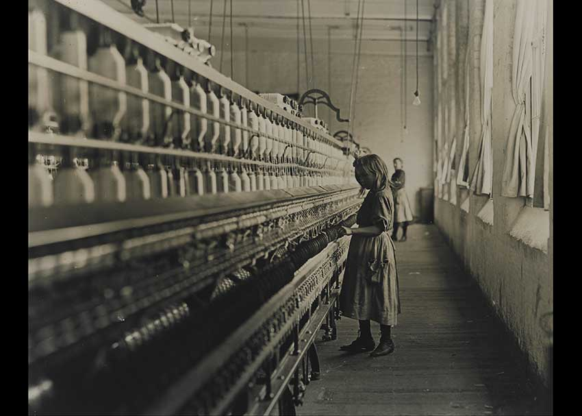 LIttle girl working at a bobbin michine at a mill