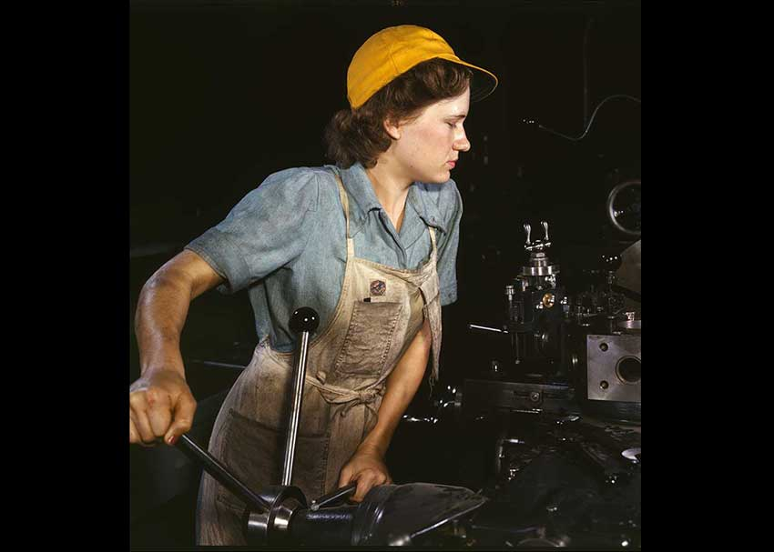 Woman in overalls with a yellow hat at a lathe