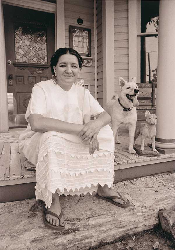 Black and white photo of Sandra Cisneros sitting on porch smiling, in white dress and with two dogs