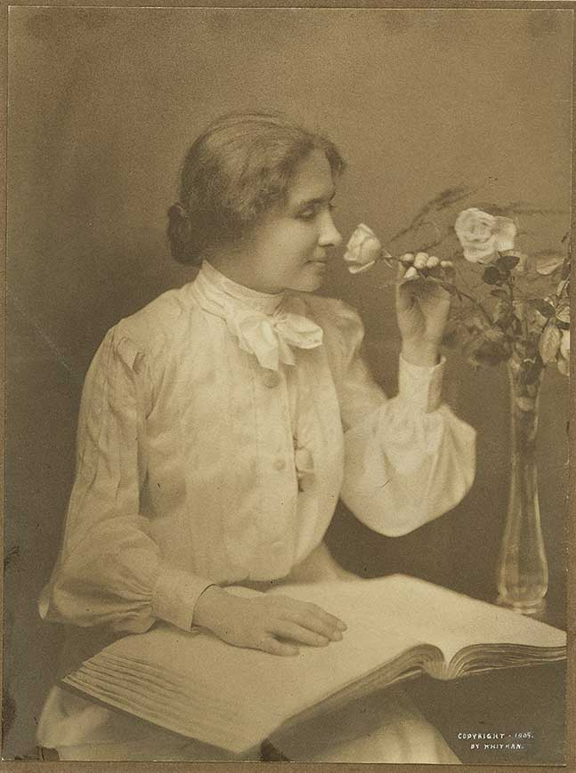 Portrait of Helen Keller, in formal dress, smelling a flower, and with a hand resting on a book in braille.
