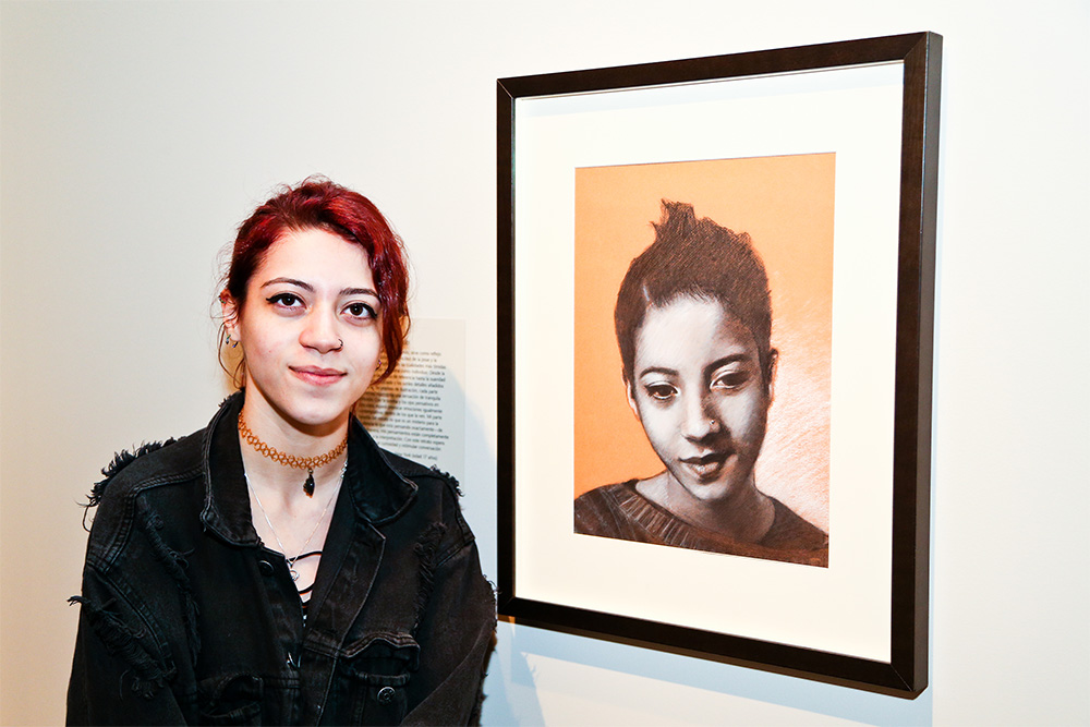 young woman standing next to her self-portrait