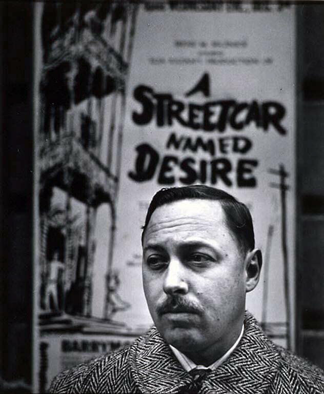 "Black and white image of a man looking into the distance and standing in front of a sign that says ""A Streetcar Named Desire"""