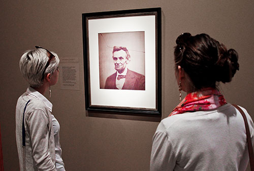 Two visitors looking at portrait of LIncoln