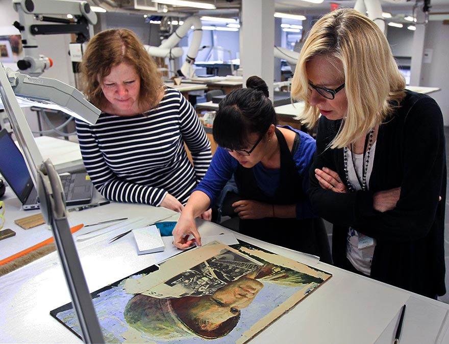 Conservators perform  an initial  examination of a painting scheduled for treatment.