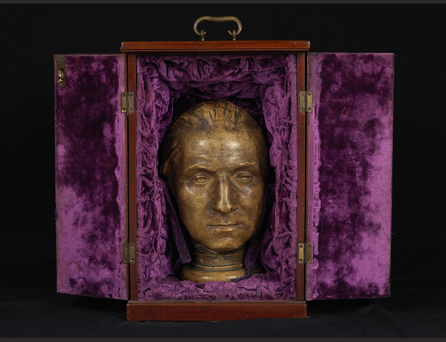 Head of a man (George Washington in a box within purple drapes.