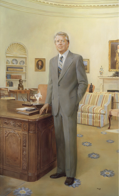 Full length portrait of a man standing by a desk