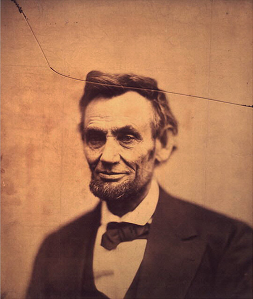 photograph of a man in a dark suit with a crack in the photo