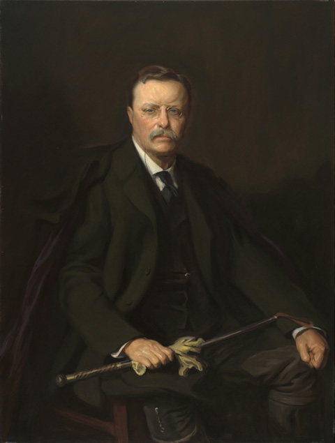 Man in a dark suit against a dark background, holding a walking stick