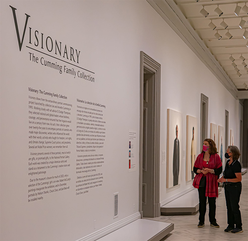 two people walking through a gallery